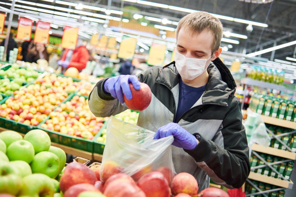 mężczyzna w masce i rękawicach ochronnych przeciwko koronawirusowi kupujący jedzenie w sklepie