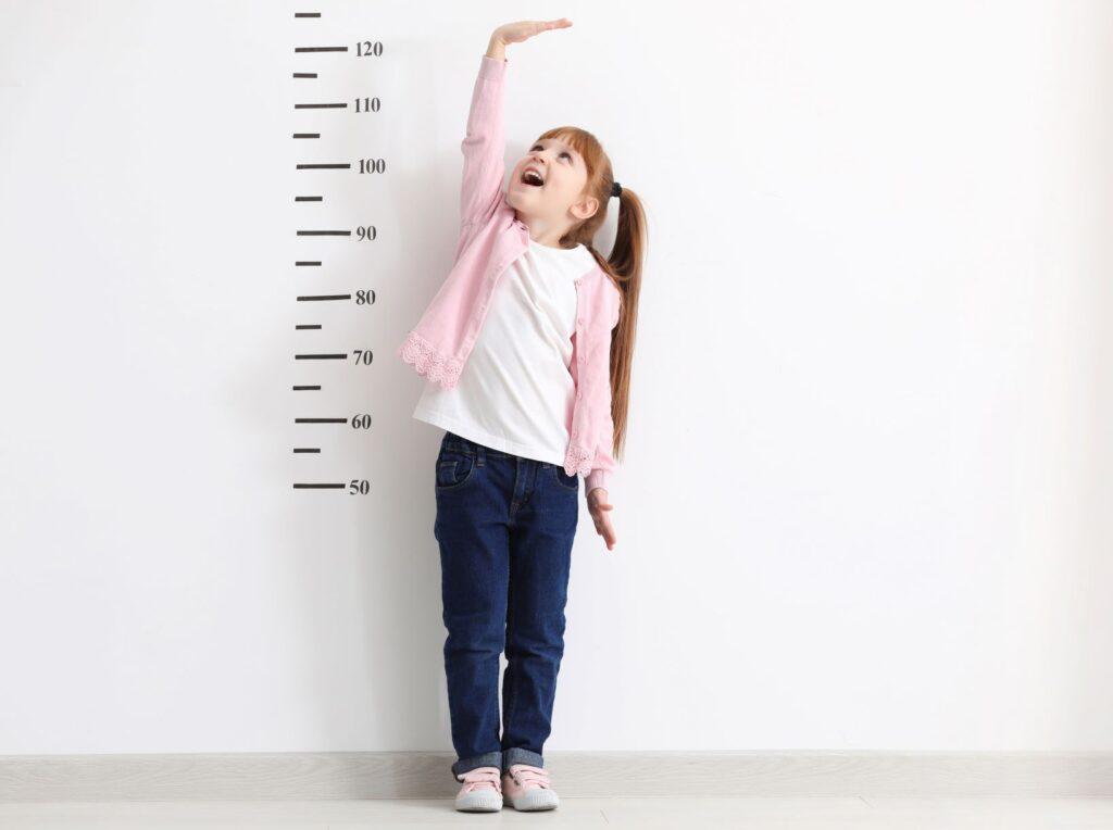 dziewczynka sprawdza swój wzrost stojąc przy ścianie
