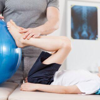 chłopiec ćwiczący na niebieskiej piłce